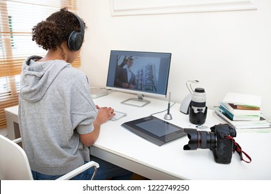 Rear view of young media technology student working on home desk with professional photographic sound equipment, indoors. Black female creative college with picture on screen, lifestyle.