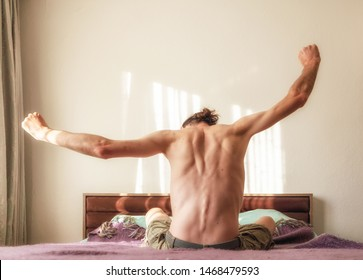 Rear view of young naked man stretching muscles on the bed in the bedroom in the morning. Healthy lifestyle concept.