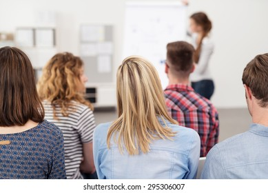 Rear View of Young Office Employees in a Business Meeting Inside the Office, Listening to Someone Presenting Something.