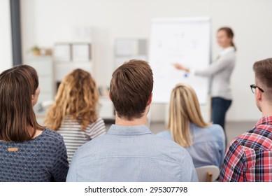 Vue arrière de jeunes employés de bureau dans des tenues décontractées Écoutant un responsable principal Expliquant quelque chose à l'aide d'illustrations.