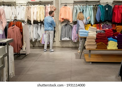 Rear view of young people choosing new clothes in clothing store in the mall