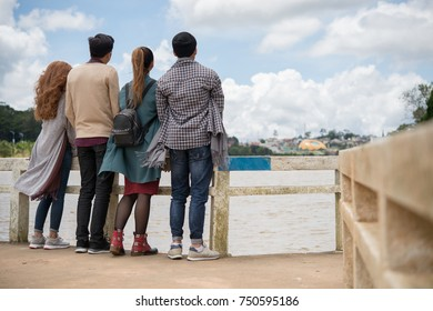 Rear view of young people enjoying the view of the river and city from the bridge