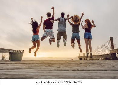 Rear view of young people jumping at the beach during sunset. Group of friends enjoying at the beach.