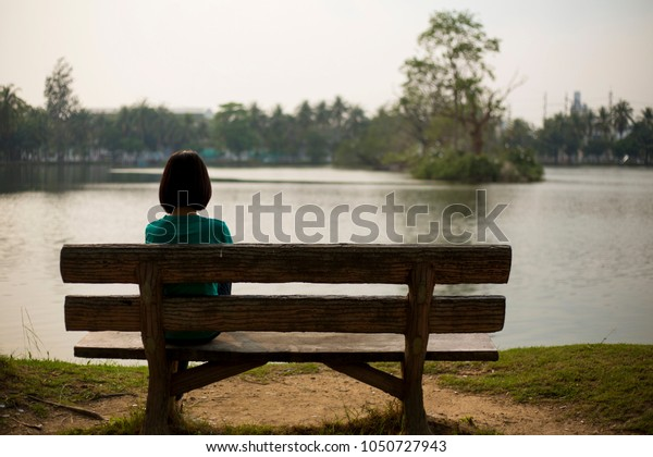Rear view of young pretty woman sitting alone on a chair in front of the sea with feeling lonely waiting for somebody, space for text
