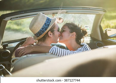 Rear view. A young romantic couple kissing in a convertible car on a country road. Backlit shot with flare