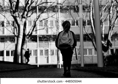 Rear view of young school girl carry a school bag walking alone  by herself to school in urban city street. Education concept. Real people.  Copy space