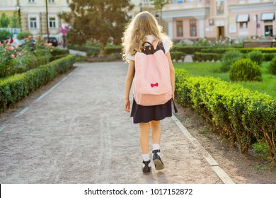 Rear view of young schoolgirl in uniform with backpack going to school