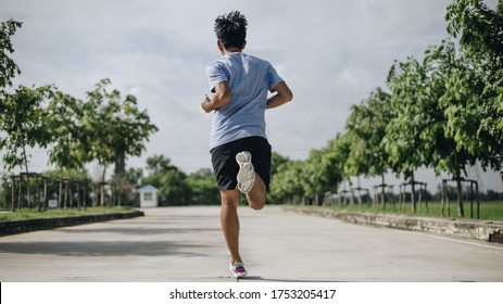 Rear View young sporty asian man running at road , Healthy exercise lifestyle Concept