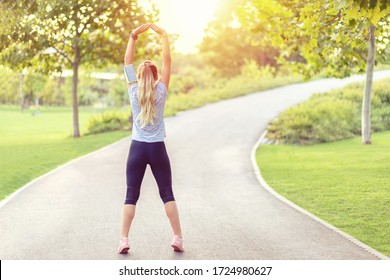 Rear view of young sporty woman jogging in empty city park due to social distancing measures – healthy girl stratching arms outdoor in nature before running – balance and meditation concept
