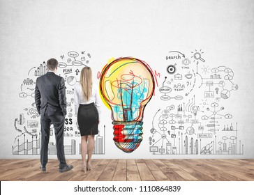Rear view of young and successful business partners wearing suits looking at a bright colorful light bulb with business scheme icons drawn on a concrete wall