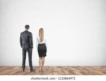 Rear view of young and successful business partners wearing suits looking at a blank concrete wall in front of them. Office lifestyle and marketing concepts. Mock up
