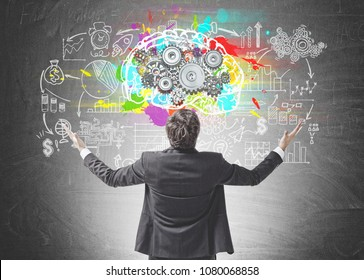 Rear view of a young successful businessman standing with hands in the air celebrating a business victory. A blackboard with a colorful brain sketch. Gears on it