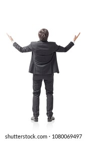 Rear view of a young successful businessman standing with hands in the air celebrating a business victory. An isolated portrait