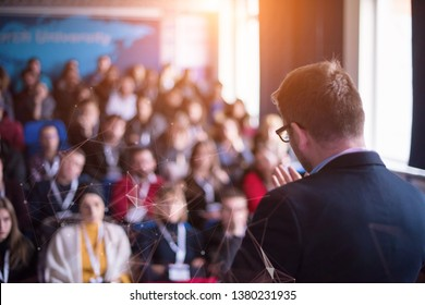 rear view of young successful businessman at business conference room with public giving presentations. Audience at the conference hall. Entrepreneurship club