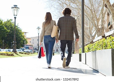 Rear view of a young tourist couple on vacation in a destination city carrying shopping bags and holding hands.