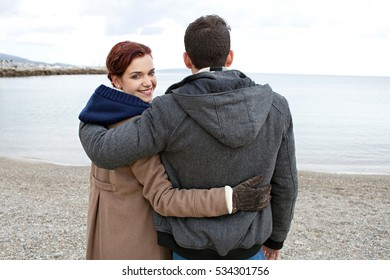 Rear view of a young tourist couple hugging, girl turning smiling looking at camera on a winter beach, contemplating the sea on holiday, nature outdoors.  Recreation travel lifestyle, coast exterior.