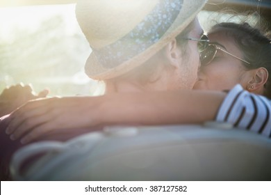Rear view. A young trendy couple kissing in a convertible car on a country road. Backlit shot with flare