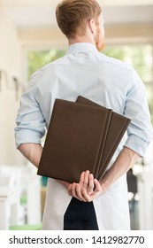 Rear view of young waiter holding menus while standing at restaurant