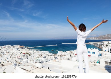 Rear view of young woman with arms outstretched, looking at the cityscape of Mykonos island, Greece. Copy space.