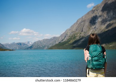 rear view of young woman with backpack looking at majestic Gjende lake, Besseggen ridge, Jotunheimen National Park, Norway