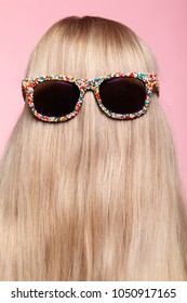 Rear view of young woman. Blond stright hair with fun sunglasses.