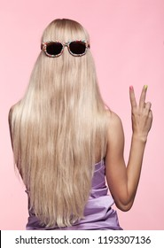 Rear view of young woman. Blond stright hair with fun sunglasses.Female finger nails with bright manicure