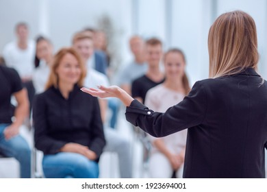 rear view. young woman doing a report for a group of young people