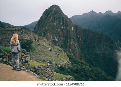 Rear view of young woman enjoying amazing scenery of high hills and mountains during trekking wanderlust.Professional female tourist admiring beautiful nature during hiking trip in Salkantay