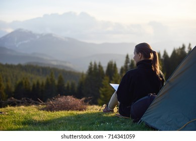 Rear view of young woman enjoying sunset in the mountains with a book near the tent