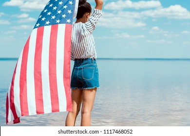 rear view of young woman holding american flag in front of sea, independence day concept