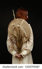 rear view of young woman holding dry reed and posing
