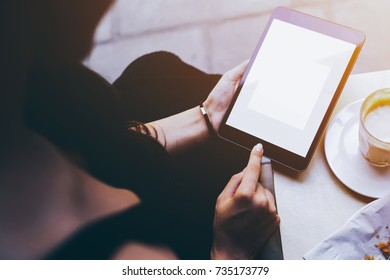 Rear view of young woman is holding digital tablet with mock up blank copy space screen for your text message. Young hipster girl reading information on website while is browsing internet on touch pad