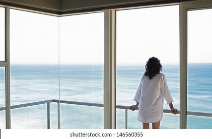 Rear view of young woman looking at sea view from balcony at resort