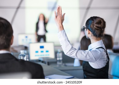 Rear view of young woman raised her hand during presentation.