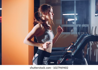 rear view of a young woman running on treadmill
