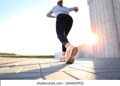 Rear view of young woman running outdoor at sunset or sunrise in city
