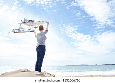 Rear view of young woman standing on sand dune contemplating the sea with arms up holding floating fabric in the breeze on holiday, outdoors. Travel wellbeing healthy female, freedom lifestyle.