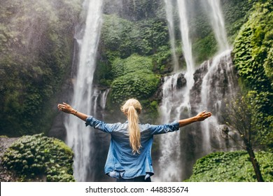Rear view of young woman standing in front of waterfall with her hands raised. Female tourist with her arms outstretched looking at waterfall.