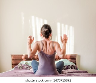 Rear view of young woman stretching muscles on the bed in the bedroom in the morning. Healthy lifestyle concept.