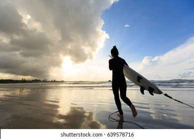Rear view of young woman surfer with white surfboard on a beach at sunrise