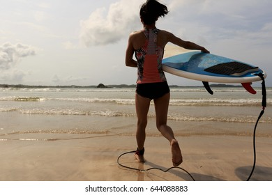 Rear view of young woman surfer with white surfboard running to the sea