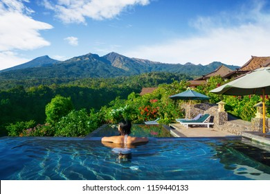 Rear view of young woman in the swim pool while enjoying Rinjani mountain landscape