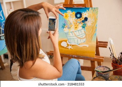Rear view of a young woman taking a photo of her most recent painting to share it and sell it online