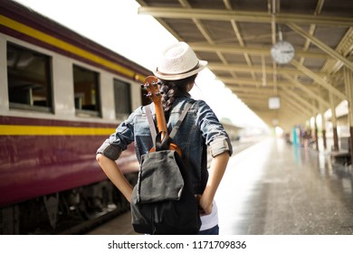 Rear view of young woman, tourist girl with backpack and guitar walking at the railway station,  Travel and holidays, Backpacker concept, vintage train,blurred background