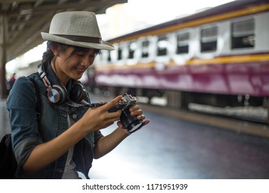 Rear view of young woman, tourist girl with backpack taking photo with her camera of the view check her photo and smile happily, at the railway station,  Travel and holidays, Backpacker concept,