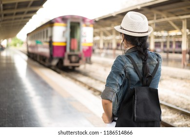 Rear view of young woman, tourist girl with backpack looking at the train as it go next station ,  Travel and holidays, Backpacker concept, vintage train,blurred background