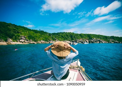 Rear view of young woman traveler with hat relaxing on speed boat at similan islands in Andaman sea at Phang Nga province near Phuket and Krabi in southern of Thailand. Summer Relax