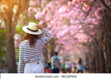 Rear view of young woman trying to selfie herself in a park with pink trumpet trees flower.