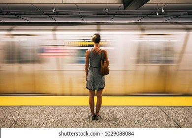 Rear view at young woman waiting for subway train in New York City, USA