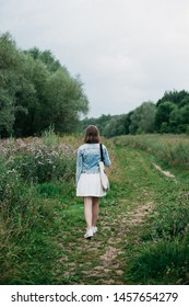 Rear view of young woman walking alone in field during summer overcast evening